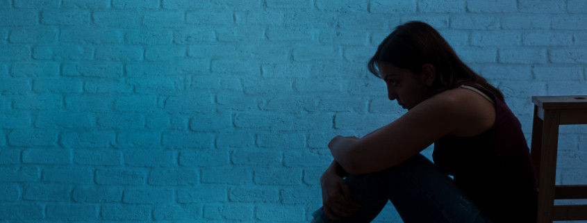 Unhappy and lonely woman silhouette in front of a wall. She sits on floor and thinks alone. Negative human expression.