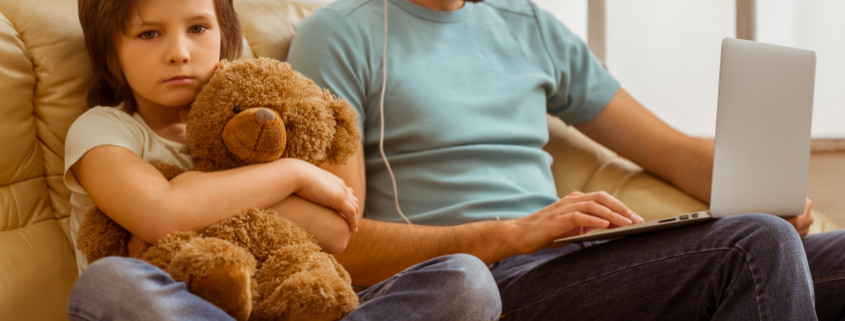 A sad little boy looking in camera and hugging a teddy bear while his father using a laptop